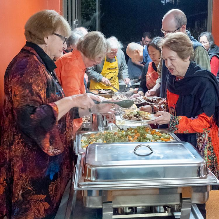 People getting food at a social dinner