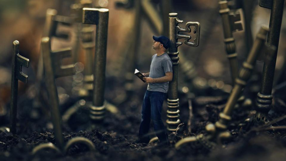 A man holding a bible is surrounded by keys